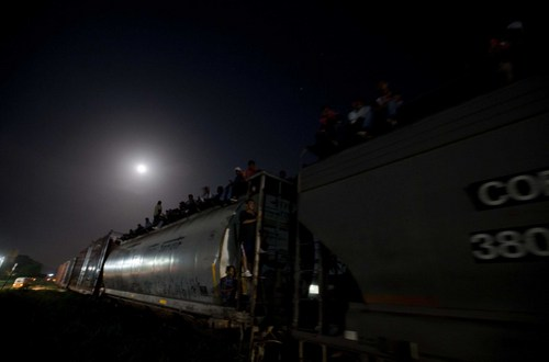 In this July 11, 2014 photo, Central American migrants wait on a stopped freight train during their journey toward the U.S.-Mexico border after reports that robbers had boarded the train and where stealing from the migrants, in Chahuites, Mexico. The police stopped and checked the train and eventually let it go as nothing out of the ordinary was found. (AP Photo/Eduardo Verdugo)