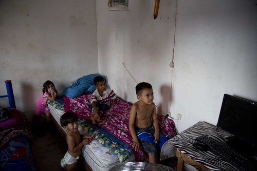 "In this July 10, 2014, photo, children watch television at the ""Todo por Ellos"" shelter for migrant children in Tapachula, Mexico. Once detained the border the U.S. generally releases unaccompanied children to parents or relatives while their cases take years to wend through overwhelmed immigration courts. That reality gave rise to rumors of a new law or amnesty for children. (AP Photo/Eduardo Verdugo)"