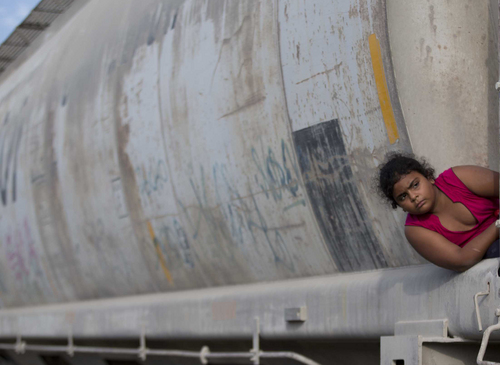 In this Saturday, July 12, 2014 photo, a young migrant girl waits for a freight train to depart on her way to the U.S. border, in Ixtepec, Mexico. Immigrants' rights advocates in the U.S. say they are seeing more children from Central America who are not only fleeing gang recruitment and random violence, but who have been targeted themselves. (AP Photo/Eduardo Verdugo)