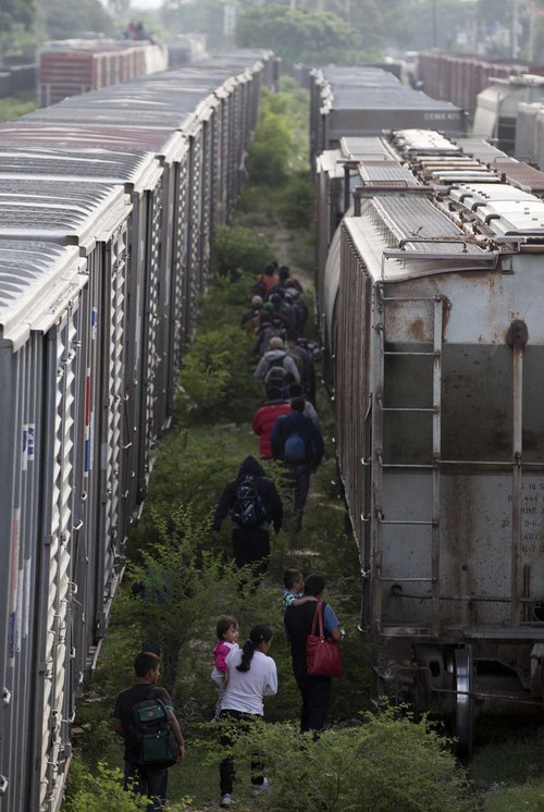In this July 12, 2014, photo, migrants walk in between parked trains after getting off one, during their journey toward the U.S.-Mexico border in Ixtepec, southern Mexico. Tens of thousands of unaccompanied minors, the vast majority from Guatemala, El Salvador and Honduras, have been apprehended at the U.S. border from last October to June, according to the Border Patrol. That's more than double the same period last year. (AP Photo/Eduardo Verdugo)