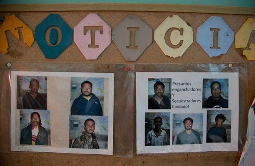 In this July 10, 2014, photo, pictures of alleged kidnappers, are displayed on a bulletin board in a shelter in Tapachula, Mexico. Smugglers are profiting from the rising violence in gang-ridden cities of Central America, and the yearning of families to be reunited; parents often head north to find work and save money to send for their children, sometimes years later.  (AP Photo/Eduardo Verdugo)