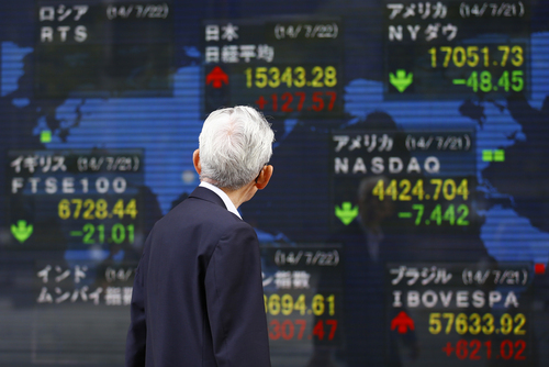 A man watches an electronic stock indicator in Tokyo, Tuesday, July 22, 2014. Asian shares rose Tuesday as tensions over the downing of a passenger jet in Ukraine eased after pro-Moscow separatists released a train packed with bodies and handed over the aircraft's black boxes. Japan's Nikkei 225 stock index added 0.8 percent to 15,343.28 as trading resumed after Monday's public holiday. (AP Photo/Shizuo Kambayashi)