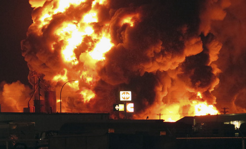 CORRECTION TO REMOVE REFERENCE THAT POLICE ATTRIBUTED THEM TO BARRELS - A fire burns at Red River Supply, an oil supply company, in an industrial part of Williston, N.D., in the early hours of Tuesday, July 22, 2014. The site is near three oil companies and a rail line, just east of Williston's downtown. Explosions could be seen and heard at the scene, but it wasn't immediately clear what caught on fire. No injuries were immediately reported.  (AP Photo/Josh Wood)