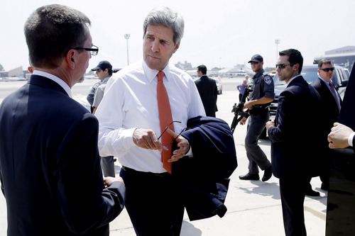 U.S. Secretary of State John Kerry, center, talks with U.S. Embassy Deputy Chief of Mission Bill Grant after his arrival in Tel Aviv, Israel, Wednesday, July 23, 2014. Kerry is meeting with U.N. Secretary-General Ban Ki-moon, Israeli Prime Minister Benjamin Netanyahu, and Palestinian Authority President Mahmoud Abbas as efforts for a cease-fire between Hamas and Israel continues. (AP Photo/Pool)