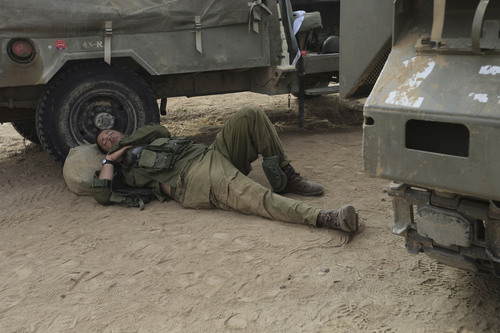 An Israeli soldier sleeps near the border of Israel and the Gaza Strip Wednesday, July 23, 2014. Israeli troops battled Hamas militants on Wednesday near a southern Gaza Strip town, sending Palestinian residents fleeing, as the U.S. secretary of state presses ahead with top-gear efforts to end the conflict that has killed hundreds of Palestinians and tens of Israelis. (AP Photo/Tsafrir Abayov)