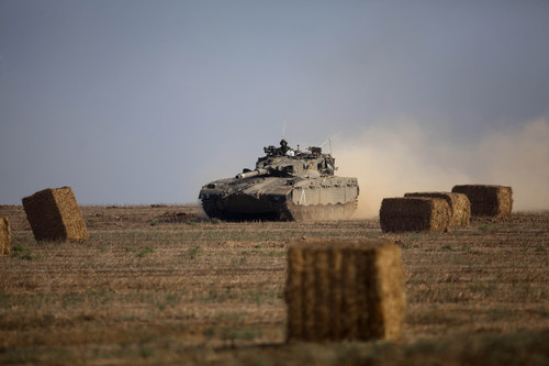 An Israeli tank runs between haystacks near the Israel and Gaza border Wednesday, July 23, 2014. Israeli troops battled Hamas militants on Wednesday near a southern Gaza Strip town, sending Palestinian residents fleeing, as the U.S. secretary of state presses ahead with top-gear efforts to end the conflict that has killed hundreds of Palestinians and tens of Israelis. (AP Photo/Dusan Vranic)