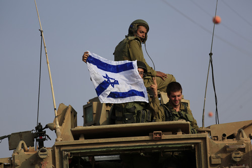 Israeli soldiers display national flag on top of an armored personnel carrier near the border of  Israel and Gaza Strip Wednesday, July 23, 2014. Israeli troops battled Hamas militants on Wednesday near a southern Gaza Strip town, sending Palestinian residents fleeing, as the U.S. secretary of state presses ahead with top-gear efforts to end the conflict that has killed hundreds of Palestinians and tens of Israelis. (AP Photo/Tsafrir Abayov)