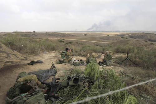 Israeli soldiers observe the border Gaza Strip Wednesday, July 23, 2014. Israeli troops battled Hamas militants on Wednesday near a southern Gaza Strip town, sending Palestinian residents fleeing, as the U.S. secretary of state presses ahead with top-gear efforts to end the conflict that has killed hundreds of Palestinians and tens of Israelis. (AP Photo/Tsafrir Abayov)