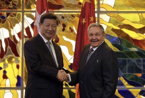 Cuba's President Raul Castro, right, shakes hands with China's President Xi Jinping during a meeting at Revolution Palace in Havana, Cuba, Tuesday, July 22, 2014. Xi Jinping is in an official state visit to Cuba. (AP Photo/Cubadebate, Ismael Francisco)