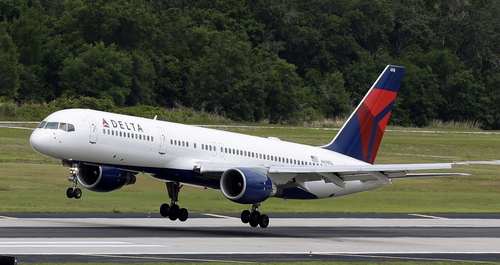 In this May 15, 2014 photo, a Delta Air Lines Boeing 757-232 lands at Tampa International Airport in Tampa , Fla. Delta reports quarterly financial results on Wednesday, July 23, 2014. (AP Photo/Chris O'Meara)