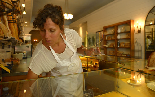 Leah Hogsten  |  The Salt Lake Tribune Eva's Bakery manager Ruby Johnson rearranges the pastry case. The Boulangerie offers pastries, croissants, pies, sandwiches and artisan breads,  July 16, 2014.