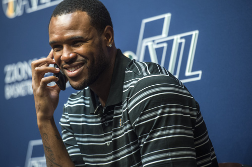 Chris Detrick  |  The Salt Lake Tribune Utah Jazz's Trevor Booker gives a radio interview over the phone during a press conference at the Zions Bank Basketball Center Tuesday July 22, 2014.
