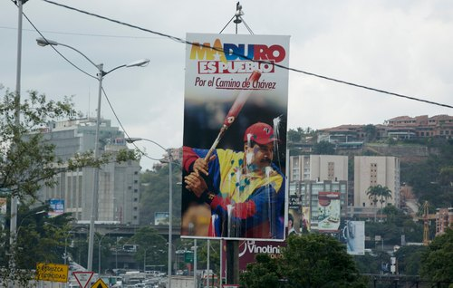 """In this  July 15, 2014, photo, a defaced billboard promoting Venezuela's President Nicolas Maduro with a message that reads in Spanish; """"Following in Chavez's footsteps,"""" towers over a main highway in Caracas, Venezuela. Announcements of foiled coups have long been a part of the Chavista discourse, but lately they have become more frequent and elaborate. Opponents say the drumbeat of alleged conspiracies helps the administration shift attention away from domestic problems such as soaring prices and rising crime.  (AP Photo/Fernando Llano)"""