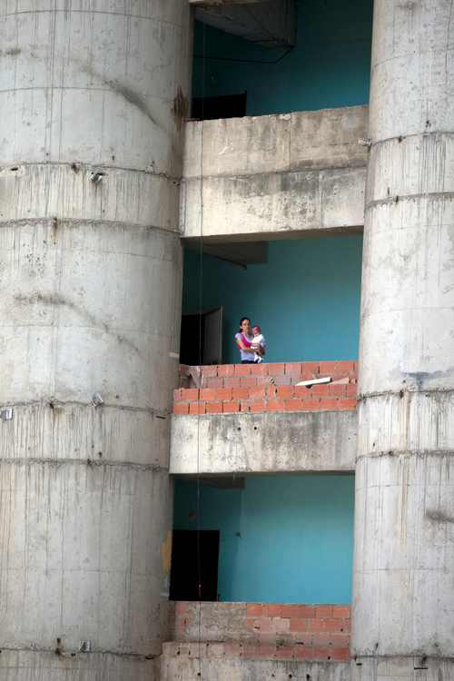A woman holds her baby outside of her apartment at the the world's tallest slum, a half-built skyscraper that was abandoned in the 1990s and was transformed by squaters into a vertical ghetto, in Caracas, Venezuela, Tuesday, July 22, 2014. Tuesday saw the beginning of the end for one of Caracas' strangest landmarks. Officials and armed soldiers began moving out the first of thousands of squatters who have lived for nearly a decade in a soaring, half-built skyscraper in the heart of Caracas. (AP Photo/Fernando Llano)