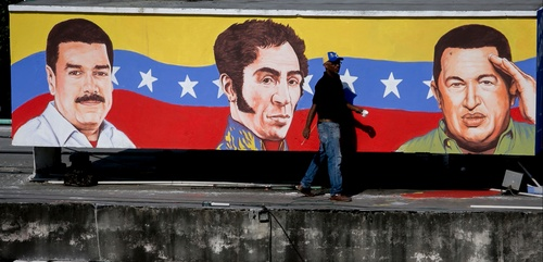 FILE - In this Feb. 4, 2014, file photo, a man walks in front of a mural with painted images of Venezuela's President Nicolas Maduro, left, independence hero Simon Bolivar and late President Hugo Chavez, in Caracas, Venezuela. Announcements of foiled coups and plots against the government have long been a part of the Chavista discourse. A study by the Caracas-based newspaper Ultimas Noticias counted 63 alleged assassination plots between when Chavez took office in 1999 and his death in 2013. Since then, such claims have come even more frequently. President Nicolas Maduro's government has denounced more than a dozen purported plots since coming to power 15 months ago. (AP Photo/Alejandro Cegarra, File)