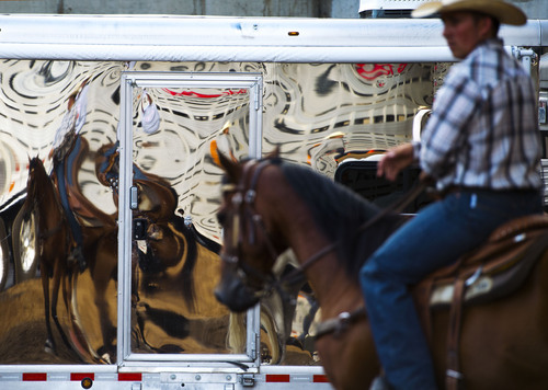 Steve Griffin     The Salt Lake Tribune   Cowboys and cowgirls are reflected in a chrome horse trailer as they warm up their horses outside EnergySolutions Arena during the Days of '47 Rodeo at  in Salt Lake City, Utah Wednesday, July 23, 2014.