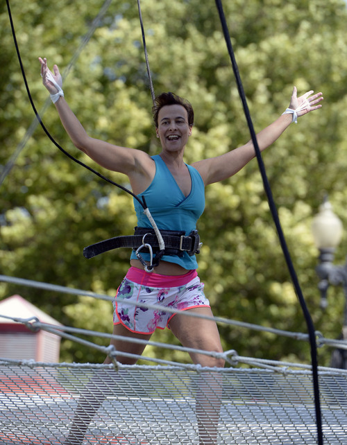 Al Hartmann  |  The Salt Lake Tribune  Utah Flying Trapeze is open at the the south side of Pioneer Park Wednesday July 23.  Kristen Atwell of Scottsdale, AZ , takes a bow to the crowd after performing an aerial trick.   A trapeze set complete with safety harnesses, nets and instruction will be offered to the public throughout weekdays by the Utah Flying Trapeze group.