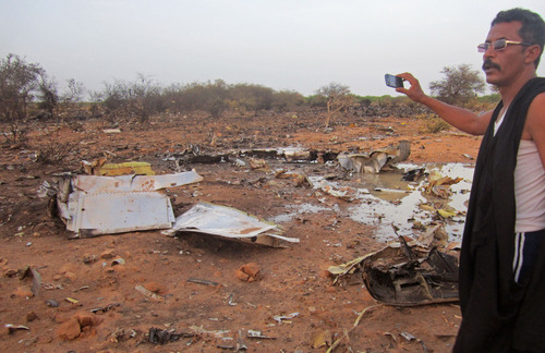 This photo provided on Friday, July 25, 2014,  by the Burkina Faso Military shows  a man at the site of the plane crash in Mali. French soldiers secured a black box from the Air Algerie wreckage site in a desolate region of restive northern Mali on Friday, the French president said. Terrorism hasn't been ruled out as a cause, although officials say the most likely reason for the catastrophe that killed all onboard is bad weather. At least 116 people were killed in Thursday's disaster, nearly half of whom were French. (AP Photo/Burkina Faso Military)