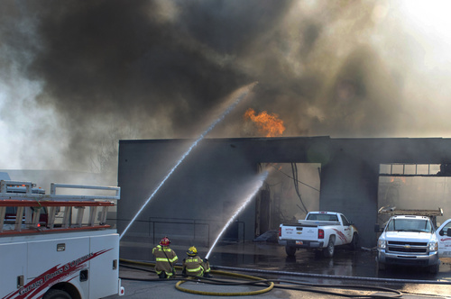 Rick Egan  |  The Salt Lake Tribune Firefighters spray hot spots on a business at 2481 South 1060 West in Woods Cross on Friday.