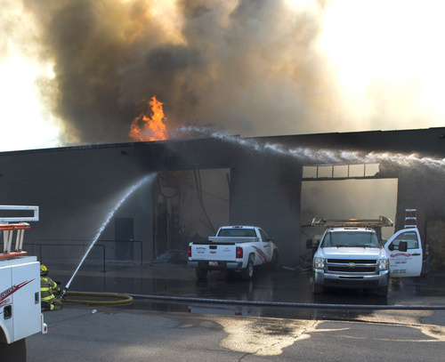 Rick Egan  |  The Salt Lake Tribune  Firefighters spray hot spots on a business at 2481 South 1060 West in Woods Cross, Friday, July 25, 2014