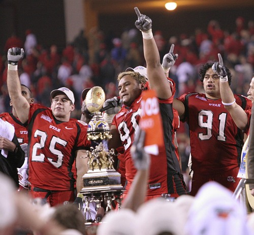 Utah players from left Morgan Scalley (25), Sione Pouha (90) and Jonathan Fanene (91) celebrate during the trophy presentation after defeating Pittsburgh, 35-7, at the Fiesta Bowl, Saturday, Jan. 1, 2005, in Tempe, Ariz. (AP Photo/Rick Hossman)