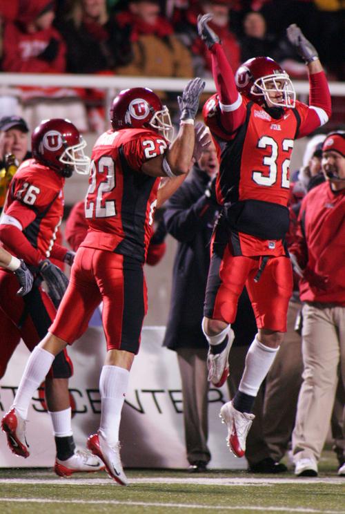 Utah's Eric Weddle (32) celebrates an interception in the end zone. Teammate Bo Nagahi at left. Utah vs. BYU college football. Photo by Trent Nelson; 11.20.2004