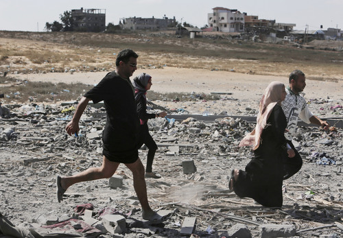 Palestinians run when they hear an Israeli tank movement from its position behind the hill, close to the border with Israel, as they return to inspect damage to their houses during a 12-hour cease-fire in Beit Hanoun, northern Gaza Strip, Saturday, July 26, 2014. Thousands of Gaza residents who had fled Israel-Hamas fighting streamed back to devastated border areas during a lull Saturday to find large-scale destruction: scores of homes were pulverized, wreckage blocked roads and power cables dangled in the streets. (AP Photo/Lefteris Pitarakis)