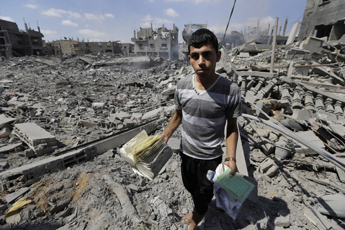 Palestinian Mahmoud Elbiss, 19, holds copies of the Holy Quran, Islam's holy book, that he salvaged from the rubble of   houses destroyed by Israeli strikes in Beit Hanoun, northern Gaza Strip, Saturday, July 26, 2014. Thousands of Gaza residents who had fled Israel-Hamas fighting streamed back to devastated border areas during a lull Saturday, and were met by large-scale destruction: scores of homes were pulverized, wreckage blocked roads and power cables dangled in the streets. (AP Photo/Lefteris Pitarakis)