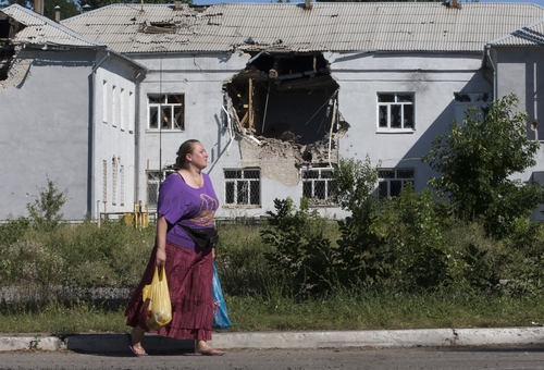 A woman walks past a damaged school in the city of Lisichansk, Luhansk region, eastern Ukraine, Saturday, July 26, 2014. Volunteers from the Donbas Battalion, a volunteer militia for a united Ukraine, told The Associated Press their units, along with the Ukrainian army, regained control of Lisichansk on Friday. (AP Photo/Dmitry Lovetsky)