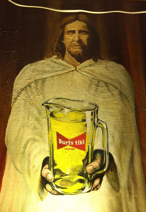 Leah Hogsten     The Salt Lake Tribune  Burt's Tiki Lounge artwork of Jesus holding a pitcher of beer adorns the wall behind the bar, April 16, 2013.