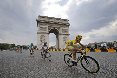 Italy's Vincenzo Nibali, wearing the overall leader's yellow jersey, passes the Arc de Triomphe during the twenty-first and last stage of the Tour de France cycling race over 137.5 kilometers (85.4 miles) with start in Evry and finish in Paris, France, Sunday, July 27, 2014. (AP Photo/Christophe Ena)