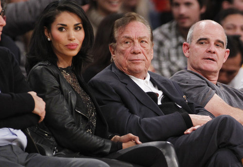 "Los Angeles Clippers owner Donald Sterling, center, and V. Stiviano, left, watch the Clippers play the Los Angeles Lakers during an NBA preseason basketball game in Los Angeles on Monday, Dec. 19, 2010. NBA spokesman Mike Bass said in a statement Saturday, April 26, 2014, that the league is in the process of authenticating the validity of the recording posted on TMZ's website. Bass called the comments ""disturbing and offensive."" (AP Photo/Danny Moloshok)"