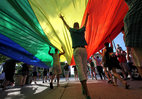 FILE - In this June 26, 2013, file photo, supporters of a U.S. Supreme Court ruling which overturned the federal Defense of Marriage Act carry a large rainbow flag during a parade around the Wisconsin State Capitol in Madison, Wis.  (AP Photo/Wisconsin State Journal, John Hart)