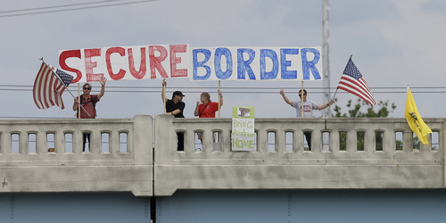 FILE - This July 18, 2014, file photo shows demonstrators with signs on an overpass in Indianapolis, to protest against people who immigrate illegally. Even as they grapple with an immigration crisis at the border, White House officials are making plans to act before November's mid-term elections to grant work permits to potentially millions of immigrants in this country illegally, allowing them to stay in the United States without threat of deportation, according to advocates and lawmakers in touch with the administration. (AP Photo/Darron Cummings, File)