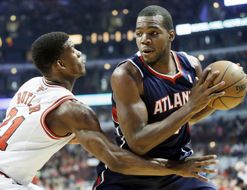 Atlanta Hawks forward Paul Millsap, right, looks to pass as Chicago Bulls guard Jimmy Butler defends during the first half of an NBA basketball game in Chicago on Saturday, Jan. 4, 2014. (AP Photo/Nam Y. Huh)