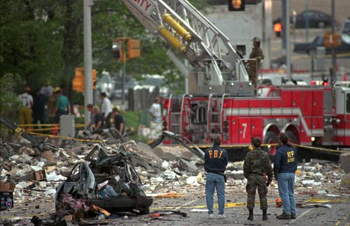 Federal Alcohol, Tobacco and Firearms agents and FBI agents survey the damage to the Alfred Murrah Federal Building in Oklahoma City Wednesday, April 19, 1995. A car bomb blast gouged a nine-story hole in the federal office building. (AP Photo/Rick Bowmer)