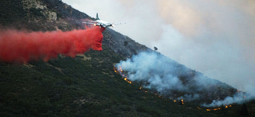 Steve Griffin  |  The Salt Lake Tribune   A plane drops a load of retardant along a burring ridge as a wildfire burns in the mountains above Levan, Utah Thursday, July 24, 2014.