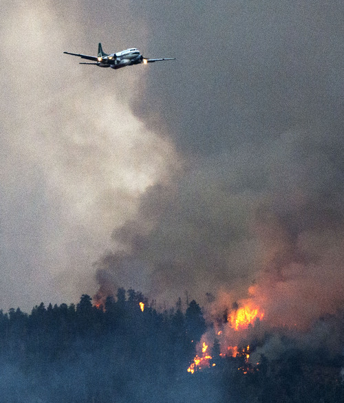 Steve Griffin  |  The Salt Lake Tribune   A plane flys along a burring ridge after dumping a load of retardant as a wildfire burns in the mountains above Levan, Utah Thursday, July 24, 2014.
