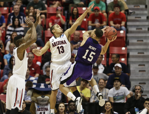 Weber State guard Davion Berry battles to get off a shot against the defense of Arizona guard Nick Johnson during the first half in a second-round game in the NCAA college basketball tournament Friday, March 21, 2014, in San Diego. (AP Photo/Gregory Bull)