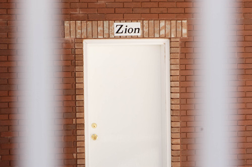 """Trent Nelson     The Salt Lake Tribune A sign reads, """"Zion"""", over the door of a home intended for the family of Warren Jeffs in Hildale, Friday April 26, 2013. The property was purchased by Willie Jessop who spent the day allowing former followers to see the inside of a compound they had previously not been allowed to enter."""