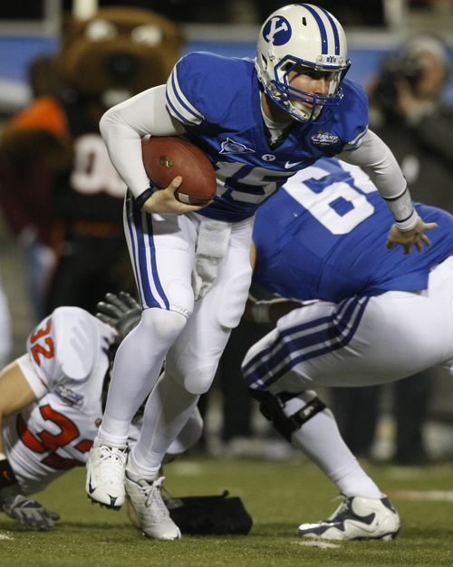 Brigham Young's Max Hall #15 runs past Oregon State's Keaton Kristick #32 during the first half of the Las Vegas Bowl at Sam Boyd Stadium Tuesday December 22, 2009.  BYU is winning the game 23-7.  Photo by Chris Detrick | The Salt Lake Tribune