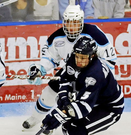 FILE - In this Jan. 4, 2009 file photo, Maine's Kyle Solomon (12) chases after New Hampshire's Kevin Kapstad, (5) during an NCAA college hockey game in Orono, Maine. Solomon is one of the plaintiffs in a class-action head injury lawsuit working its way through federal court in Chicago. The NCAA and the plaintiffs announced a settlement on Tuesday, July 29, 2014.  (AP Photo/Michael C. York, File)