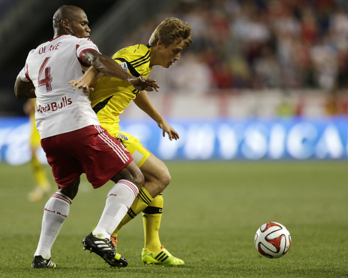 New York Red Bulls' Jamison Olave (4) and Columbus Crew's Aaron Schoenfeld compete for the ball during the second half of an MLS soccer match, Saturday, July 12, 2014, in Harrison, N.J. The Red Bulls won 4-1. (AP Photo/Julio Cortez)