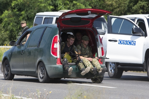 Pro-Russian rebels travel past a convoy of the OSCE mission in Ukraine outside the city of Donetsk, eastern Ukraine Wednesday, July 30, 2014. (AP Photo/Dmitry Lovetsky)