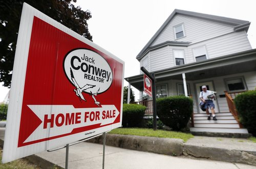 In this July 10, 2014 photo, a mailman delivers mail to a house for sale in Quincy, Mass. Getting a larger home loan is easier than getting a small one. (AP Photo/Michael Dwyer)