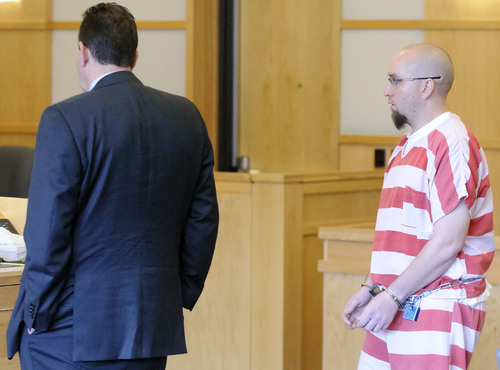 Eli Lucero  |  Pool Photo  Jason Burr, right, walks walks up the podium in First District Court on Wednesday, where his lawyer David Perry waits, to plead guilty to three felonies from an incident when he entered the Cache Valley Hospital with loaded guns.