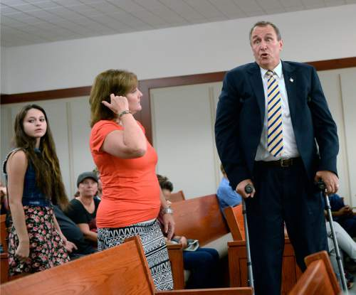 Al Hartmann  |  The Salt Lake Tribune  Former attorney general Mark Shurtleff using crutches looks for a place to sit in Judge Royal Hansen's courtroom in Salt Lake City Wednesday July 30.  His wife M'Liss, center and daughter Annie accompany him. Shurtleff and former attorney general John Swallow are charged with receiving or soliciting bribes, accepting gifts, tampering with evidence, obstructing justice and participating in a pattern of unlawful conduct.