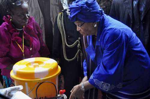 In this photo taken on Saturday, July 26, 2014, Liberia President  Ellen Johnson Sirleaf, right, demonstrates to people how to wash their hands properly in order to prevent the spread of the Ebola virus, during  Independence Day celebrations in the city of Monrovia, Liberia. Scientists from Fort Detrick say the number of Ebola cases in West Africa is much larger than official estimates indicate. Researchers from the U.S. Army Medical Research Institute of Infectious Diseases, who have worked in Sierra Leone and Liberia, say the current outbreak reaches beyond the 1,200 confirmed, suspected or probable cases and over 600 deaths that the World Health Organization has identified in West Africa as of July 23. (AP Photo/Abbas Dulleh)