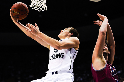 BYU guard Kyle Collinsworth attempts a shot past Loyola Marymount's Ben Dickinson during an NCAA college basketball game Saturday, Jan. 11, 2014, in Provo, Utah. (AP Photo/Daily Herald, Alex Goodlett)