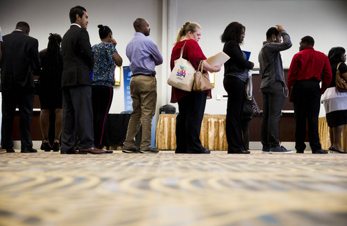 In this June 23, 2014 photo, job seekers wait in line to meet with recruiters during a job fair in Philadelphia. The government issues the July jobs report on Friday, Aug. 1, 2014. (AP Photo/Matt Rourke)